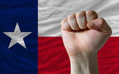 Us state flag of texas with hard fist in front of it symbolizing — Stock Photo