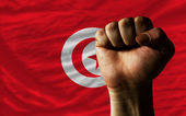 Hard fist in front of tunisia flag symbolizing power — Stock Photo