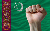 Hard fist in front of turkmenistan flag symbolizing power — Stock Photo