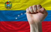 Hard fist in front of venezuela flag symbolizing power — Stock Photo