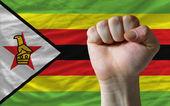 Hard fist in front of zimbabwe flag symbolizing power — Stock Photo
