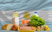 Basic food groceries in front of argentina national flag — Stock Photo