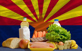 Basic food groceries in front of arizona us state flag — Stock Photo