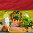Basic food groceries in front of bolivia national flag — Stock Photo