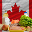 Foto Stock: Basic food groceries in front of canadnational flag