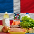 Basic food groceries in front of dominican national flag — Stok fotoğraf