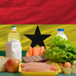 Basic food groceries in front of ghana national flag — Stock Photo