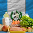 Basic food groceries in front of guatemala national flag — Stock fotografie