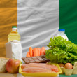 Basic food groceries in front of ivory coast national flag — Stock Photo #11032319