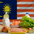 Basic food groceries in front of malaysia national flag — Stock Photo
