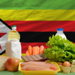 Basic food groceries in front of zimbabwe national flag — Stock Photo #11036731