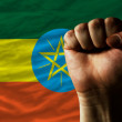 Hard fist in front of ethiopia flag symbolizing power - Stock Photo