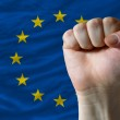 Hard fist in front of europe flag symbolizing power — Stock Photo