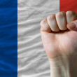 Hard fist in front of france flag symbolizing power - Stock Photo