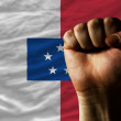 Hard fist in front of franceville flag symbolizing power - Stock Photo