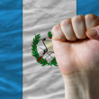 Hard fist in front of guatemala flag symbolizing power - Stock Photo
