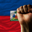 Hard fist in front of haiti flag symbolizing power - Stock Photo