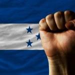 duro puño frente a bandera de honduras que simboliza el poder — Foto de Stock