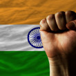Hard fist in front of india flag symbolizing power - Stock Photo