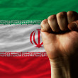 Hard fist in front of iran flag symbolizing power - Stock Photo