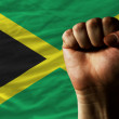 Hard fist in front of jamaica flag symbolizing power - Stock Photo