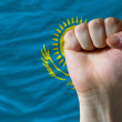 Hard fist in front of kazakhstan flag symbolizing power - Stock Photo