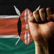 Hard fist in front of kenya flag symbolizing power - Stock Photo