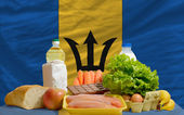 Basic food groceries in front of barbados national flag — Stock Photo