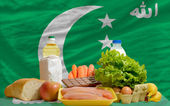 Basic food groceries in front of comoros national flag — Stock Photo