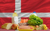 Basic food groceries in front of denmark national flag — Stock Photo