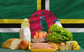 Basic food groceries in front of dominica national flag — Stock Photo