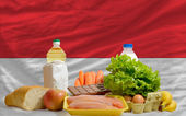 Basic food groceries in front of indonesia national flag — Stock Photo
