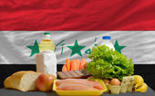 Basic food groceries in front of iraq national flag — Stock Photo
