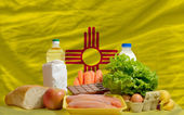 Basic food groceries in front of new mexico us state flag — Stock Photo