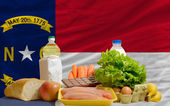 Basic food groceries in front of north carolina us state flag — Stock Photo