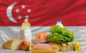 Basic food groceries in front of singapore national flag — Stock Photo