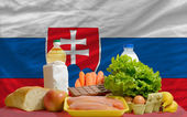 Basic food groceries in front of slovakia national flag — Stock Photo