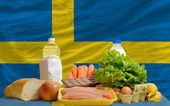 Basic food groceries in front of sweden national flag — Stock Photo