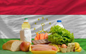 Basic food groceries in front of tajikistan national flag — Stock Photo