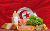 Basic food groceries in front of tunisia national flag — Stock Photo