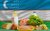 Basic food groceries in front of uzbekistan national flag — Stock Photo