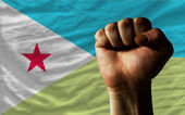 Hard fist in front of djibouti flag symbolizing power — Stock Photo