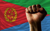 Hard fist in front of eritrea flag symbolizing power — Stock Photo