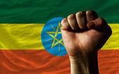 Hard fist in front of ethiopia flag symbolizing power — Stock Photo