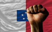 Hard fist in front of franceville flag symbolizing power — Stock Photo