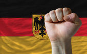 Hard fist in front of germany flag symbolizing power — Stock Photo