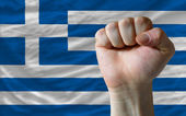 Hard fist in front of greece flag symbolizing power — Stock Photo