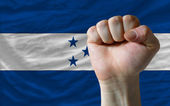 Hard fist in front of honduras flag symbolizing power — Stock Photo