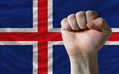 Hard fist in front of iceland flag symbolizing power — Stock Photo