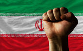 Hard fist in front of iran flag symbolizing power — Stock Photo